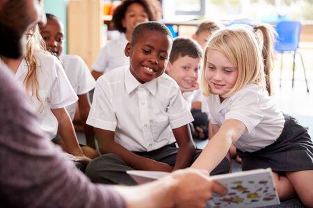 Profesor de sexo masculino leyendo la historia al grupo de alumnos de primaria vistiendo uniforme en el aula de la escuela