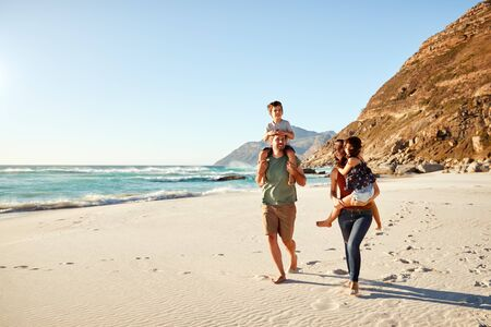 Mid adult white couple walking along on a beach on a family holiday carrying their kids, full length Stockfoto