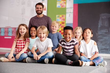 Portrait Of Elementary School Pupils Sitting On Floor In Classroom With Male Teacher