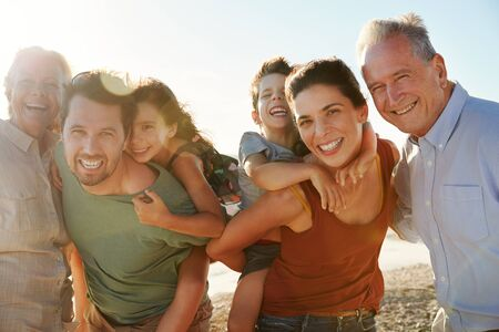 Three generation white family on a beach smiling to camera, parents piggybacking kids, close up