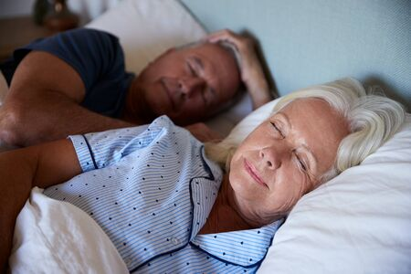 Senior white couple lying asleep in their bed, waist up, close up