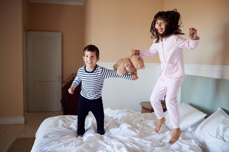 Brother and sister having fun bouncing on their parents' bed in their pyjamas, full length