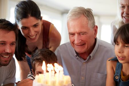 Senior white man and his family celebrating his birthday with cake and lit candles, close up