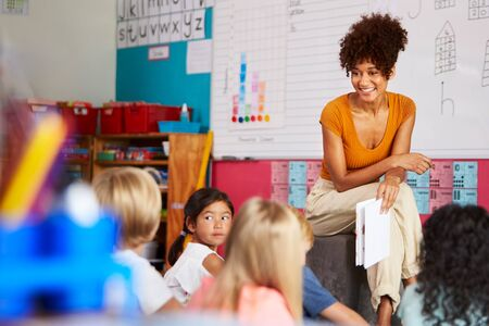 Female Teacher Reading Story To Group Of Elementary Pupils In School Classroom Imagens