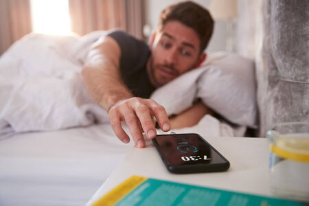 Man Waking Up In Bed Reaches Out To Turn Off Alarm On Mobile Phone 写真素材