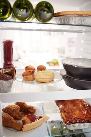 View Inside Refrigerator Of Unhealthy Takeaway Food And Beer On Shelves Foto de archivo - 128229431