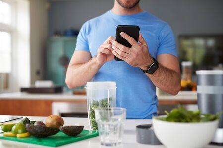 Cerca del hombre con rastreador de ejercicios para contar las calorías para la bebida de jugo posterior al entrenamiento que está haciendo
