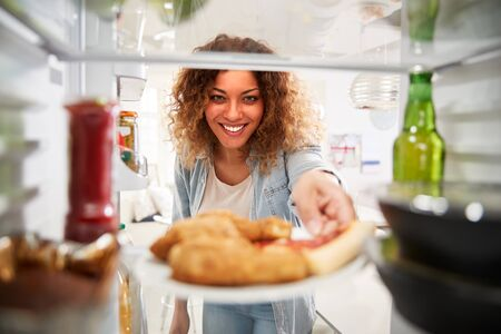 View Looking Out From Inside Of Refrigerator Filled With Takeaway Food As Woman Opens Door