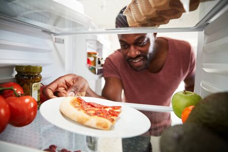 View Looking Out From Inside Of Refrigerator As Man Opens Door For Leftover Takeaway Pizza Slice Imagens