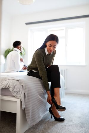 Business Couple In Bedroom Getting Ready For Work Businesswoman At Home Putting On Shoes Stock Photo