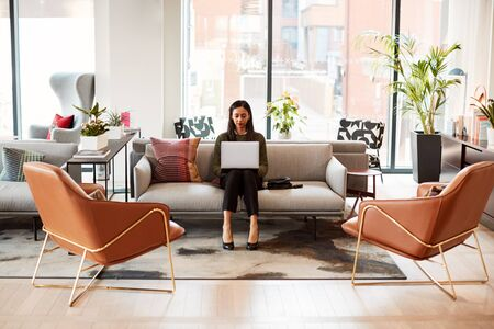 Businesswoman Sitting On Sofa Working On Laptop At Desk In Shared Workspace Office Stock Photo
