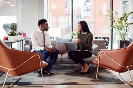 La empresaria entrevistar a un candidato de trabajo masculino en la zona de estar de la oficina moderna Foto de archivo