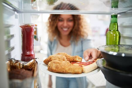 View Looking Out From Inside Of Refrigerator Filled With Takeaway Food As Woman Opens Door Foto de archivo - 128229595