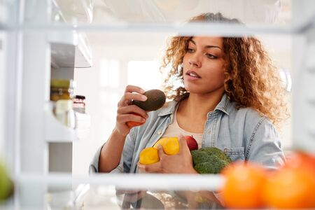 View Looking Out From Inside Of Refrigerator As Woman Opens Door And Packs Food Onto Shelves Stock fotó