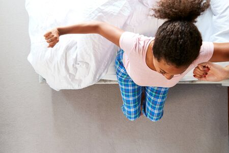 Overhead View Of Woman Wearing Pajamas Stretching As She Gets Out Of Bed At Home