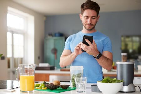 Man Using Fitness Tracker To Count Calories For Post Workout Juice Drink He Is Making