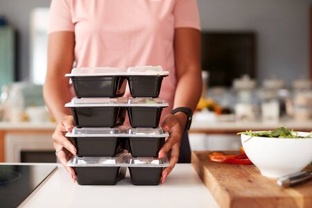 Close Up Of Woman Preparing Batch Of Healthy Meals At Home In Kitchen Banco de Imagens
