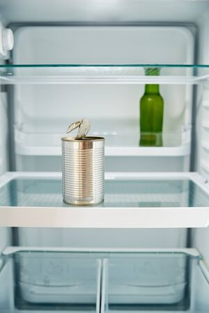 View Looking Inside Refrigerator Empty Except For Open Tin Can And Bottle Of Beer On Shelf