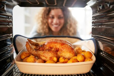 View Looking Out From Inside Oven As Woman Cooks Sunday Roast Chicken Dinner Stock Photo