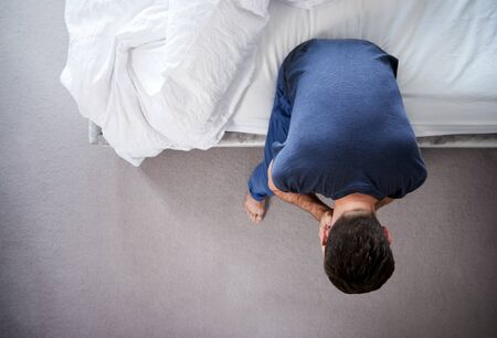 Overhead View Of Man Wearing Pajamas Suffering With Depression Sitting On Bed At Home Stock Photo