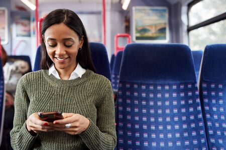 Female Passenger Sitting In Train Looking At Mobile Phone