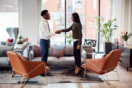 Businesswoman Shaking Hands With Male Interview Candidate In Seating Area Of Modern Office Banco de Imagens