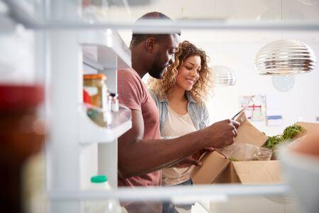 Vista che guarda fuori dall'interno del frigorifero mentre una coppia disimballa la consegna di cibo a domicilio online Archivio Fotografico