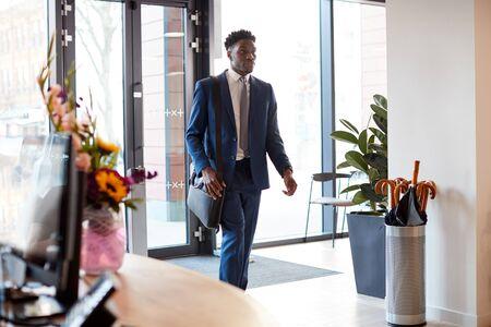 Businessman Arriving For Work At Office Walking Through Door Reklamní fotografie
