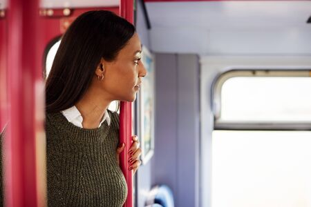 Female Passenger Standing By Doors In Train Looking Out Of Window