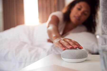 Woman Waking Up In Bed With Voice Assistant On Bedside Table Next To Her