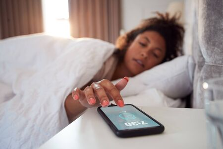 Woman Waking Up In Bed Reaches Out To Turn Off Alarm On Mobile Phone 写真素材