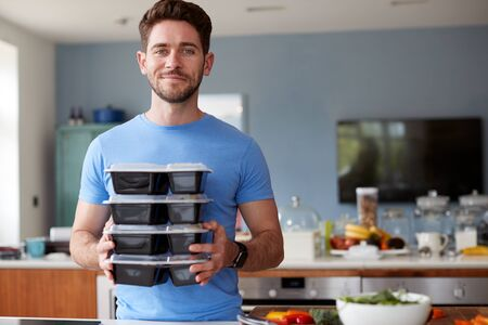Portrait Of Man Preparing Batch Of Healthy Meals At Home In Kitchen