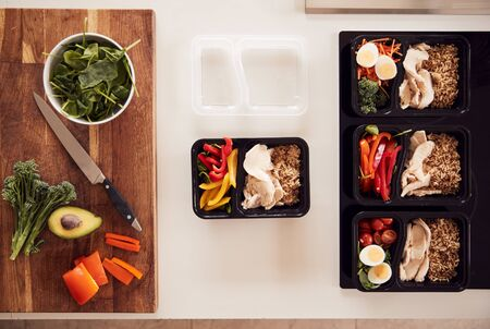 Overhead Shot Of Ingredients And Containers For Batch Of Healthy Meals At Home On Kitchen Counter