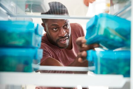 View Looking Out From Inside Of Refrigerator As Man Takes Out Healthy Packed Lunch In Container