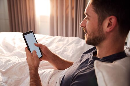 Man Sitting Up In Bed Looking At Mobile Phone After Having Woken Up