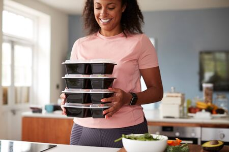 Woman Preparing Batch Of Healthy Meals At Home In Kitchen Imagens