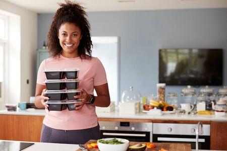 Portrait Of Woman Preparing Batch Of Healthy Meals At Home In Kitchen