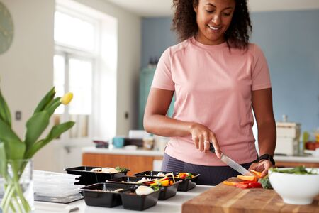 Woman Preparing Batch Of Healthy Meals At Home In Kitchen Banco de Imagens