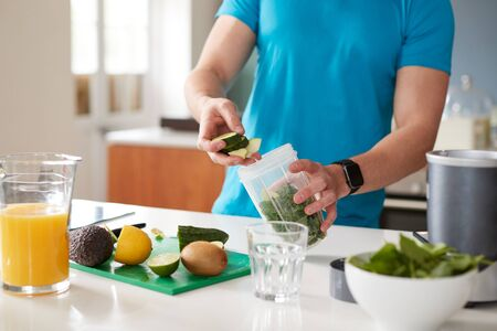 Close Up Of Man Preparing Ingredients For Healthy Juice Drink After Exercise