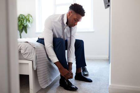 El empresario en casa sentado en la cama poniéndose los zapatos antes de irse al trabajo