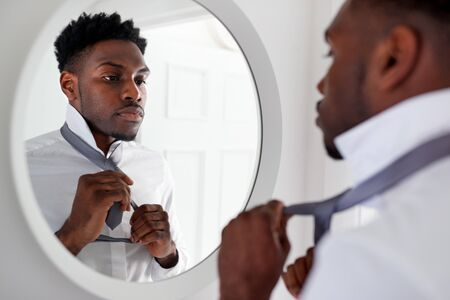 Businessman At Home Tying Necktie In Mirror Before Leaving For Work
