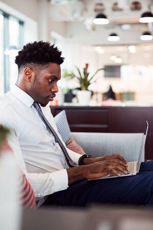 Businessman Working On Laptop At Desk In Shared Workspace Office Zdjęcie Seryjne