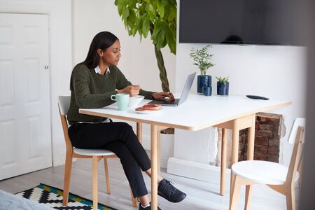 Businesswoman At Home Eating Breakfast Looking At Laptop Before Leaving For Work Zdjęcie Seryjne
