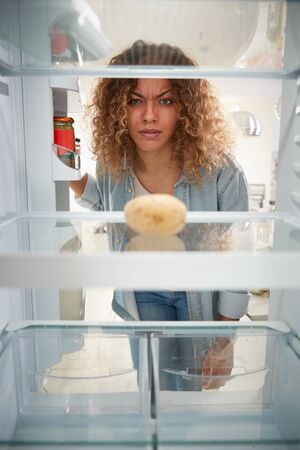 Disappointed Woman Looking Inside Refrigerator Empty Except For Potato On Shelf