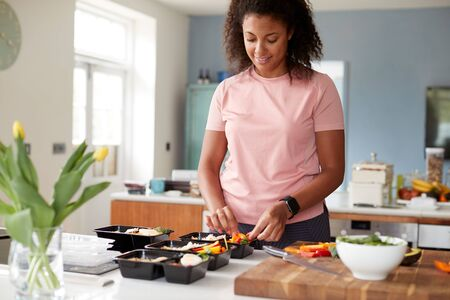 Woman Preparing Batch Of Healthy Meals At Home In Kitchen 写真素材