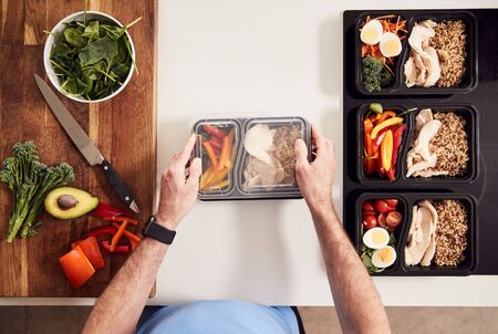 Overhead Shot Of Man Preparing Batch Of Healthy Meals At Home In Kitchen