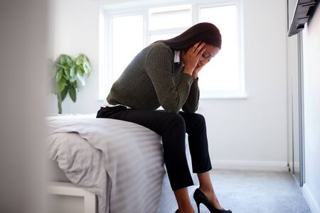Stressed Businesswoman With Head In Hands Sitting On Edge Of Bed At Home Zdjęcie Seryjne