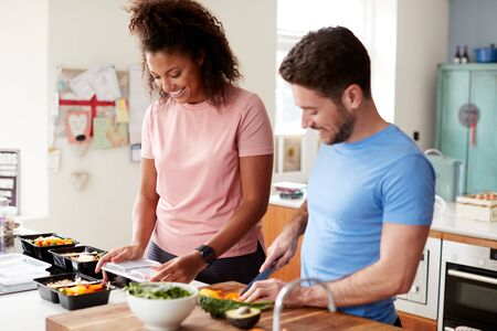 Couple Preparing Batch Of Healthy Meals At Home In Kitchen Together Zdjęcie Seryjne
