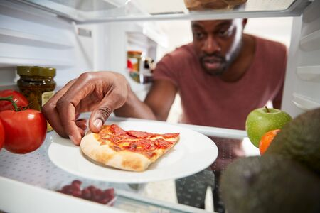 View Looking Out From Inside Of Refrigerator As Man Opens Door For Leftover Takeaway Pizza Slice Zdjęcie Seryjne