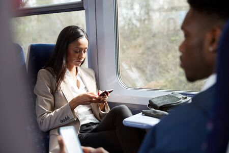 Business Passengers Sitting In Train Commuting To Work Looking At Mobile Phones